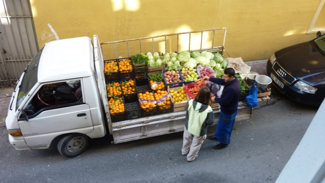 """The fruit & veggie truck that came by every few days.  I finally figured out that when I said """"five"""" and meant 5 apples, he assumed I wanted 5 kilograms of apples!  Even so, a very inexpensive and convenient way to shop.  (Our neighbor lady just lowered a basket from her 4th story window!)"""