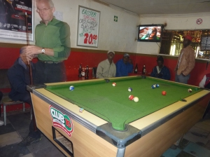 KC shooting pool at the neighborhood shebeen (bar)