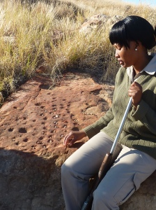 "Our guide in Mapungubwe, South Africa. Here she is explaining the ancient African ""board game"" called Makala. The board game was located on the plateau where royalty resided....And, yes that is a rifle in her hand. We had to trek through the bush to reach the Mapungubwe ruins."