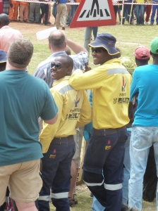 At the annual Spring Festival in Haenertsburg, South Africa.  Firefighters, representing a pine plantation,look on after their team's loss in the tug-of-war competition against another timber company's team.