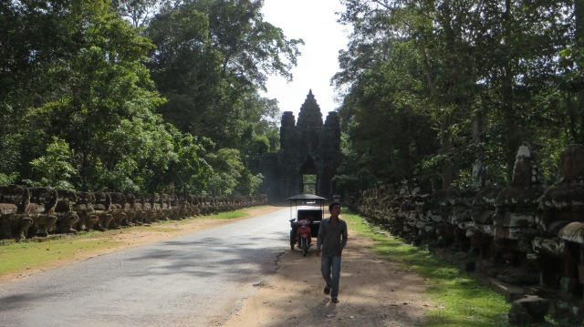 A tuk tuk and driver near one of the entrance gates to Angkor Thom, Cambodia